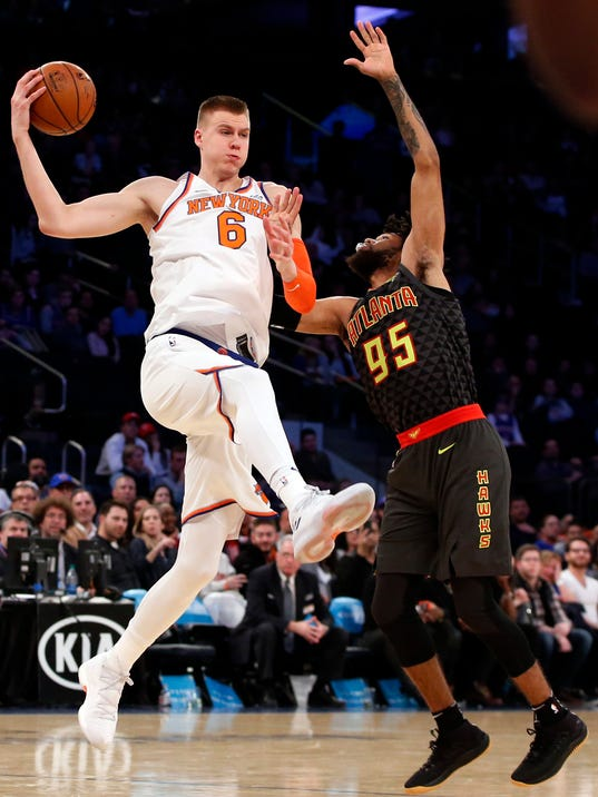 New York Knicks forward Kristaps Porzingis (6) keeps the ball from Atlanta Hawks forward DeAndre' Bembry (95) in the waning seconds of the fourth quarter of an NBA basketball game at Madison Square Garden in New York, Sunday, Dec. 10, 2017. (AP Photo/Kathy Willens)