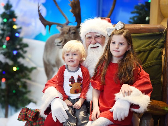 Santa Claus puts both knees to use as he poses for a photo with Myles and Willow Hertel of Brandon last week at Bass Pro Shops in Pearl.