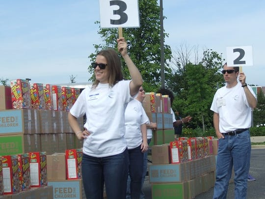 Kelsey Miller and Jeff Lawn, employees of Concord Hospitality Enterprises, hold up numbers indicating their food pickup stations are open for recipients waiting in line. Miller and Lawn were among the approximately 40 Concord employees who volunteered for the June 15 food-distribution event, held in a parking lot at Novi High School.