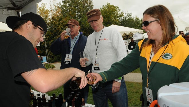 Brad Cummings of O'so Brewery Co. pours a sample of the Plover craft brewery's popular Night Train oatmeal porter for Melissa McConnell, right, of Oswego, Ill., at last year's Egg Harbor's AleFest. Also tasting are John English and Tim McCurry, both of Park Ridge, Ill. The beer (and cider and hard soda) tasting festival returns Sept. 17 for its fifth straight year.