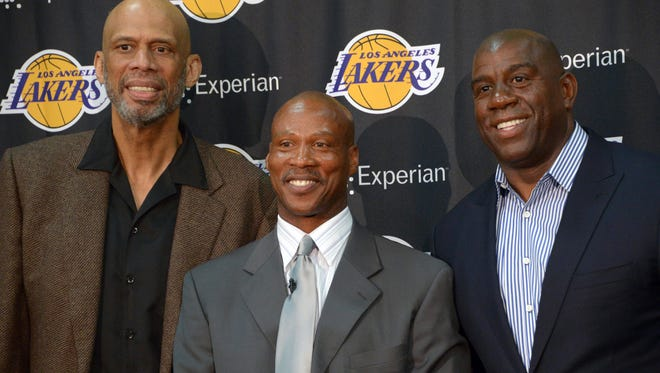 yron Scott (center) poses with Kareem Abdul-Jabbar (left) and Magic Johnson at a press conference to announce Scott as Los Angeles Lakers coach at Toyota Sports Center.