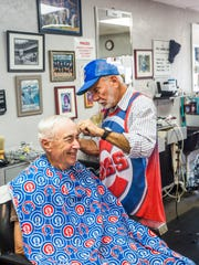 Barber Peter Apostle gives a haircut to client Ron Ricketts, of Bonita Springs, at Paul's Barber Shop in Bonita Springs on March 20.