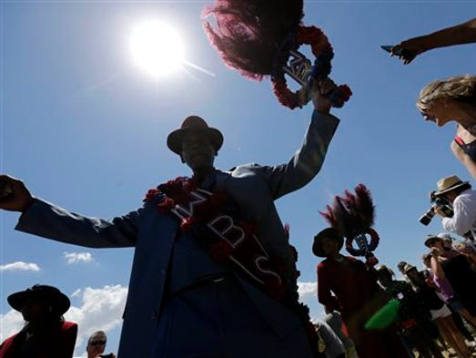 Members of the West Bank Steppers Social & Pleasure Club form a second line parade at the New Orleans Jazz and Heritage Festival in New Orleans, Saturday, May 3, 2014. (AP Photo/Gerald Herbert)
