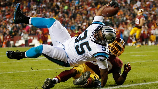 Carolina Panthers fullback Mike Tolbert (35) rolls over Washington outside linebacker Martrell Spaight (50) for a touchdown during the second half Monday. Carolina won 26-15.