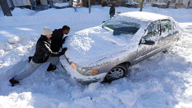 Heather Williams and Amos Goins help a neighbor get his snowbound car get unstuck near N. 53rd St. and W. North Ave. in January 2015.