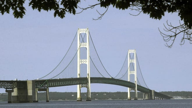 FILE - This July 19, 2002, file photo, shows the Mackinac Bridge that spans the Straits of Mackinac from Mackinaw City, Mich. Oil transport company Enbridge says Wednesday, a gap has opened between a section of its Line 5 pipeline and the lake bottom in Michigan's Straits of Mackinac. Erosion has washed away sediments beneath the pipeline, opening a gap that exceeds the 75-foot limit set under a state easement. The company says it's awaiting government permits to install screw anchors for additional support in that spot and others along the underwater line.