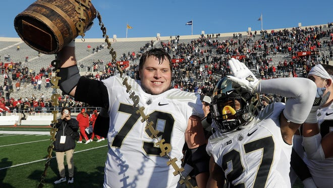Purdue's Matt McCann (79) and Navon Mosley (27) celebrates with the Old Oaken Bucket after Purdue defeated Indiana, 28-21, in an NCAA college football game, Saturday, Nov. 24, 2018, in Bloomington, Ind. (Darron Cummings)
