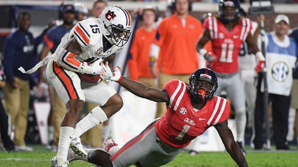 Auburn defensive back Joshua Holsey (15) intercepts a pass intended for Mississippi wide receiver A.J. Brown (1) during the second half of an NCAA college football game in Oxford, Miss., Saturday, Oct. 29, 2016.  (AP Photo/Thomas Graning)
