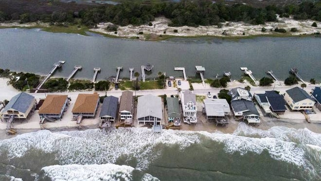 Waves wash under the homes on the southernmost tip of Pawleys Island during the July king tide on July 11, 2018. Experts say that sea level rise could threaten over 3,000 homes in Horry and Georgetown counties by 2045.