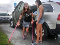 Adrianna helps her twin sister, Olivia, out of a car before school. Olivia has cerebral palsy.