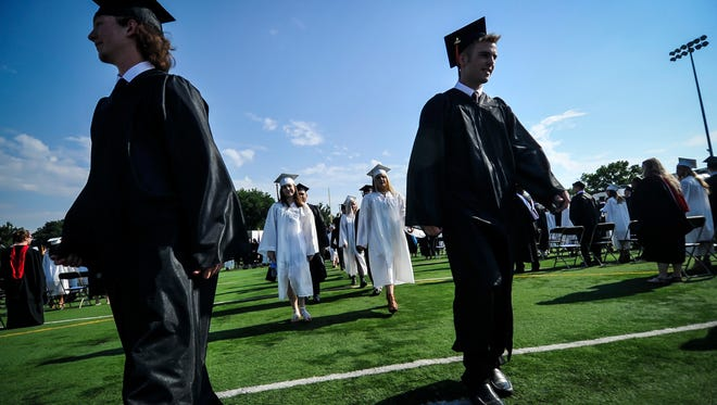 Graduates make their way to the seats during the start of the Somerville High School commencement held at Brooks Field in Somerville on June 24, 2016.