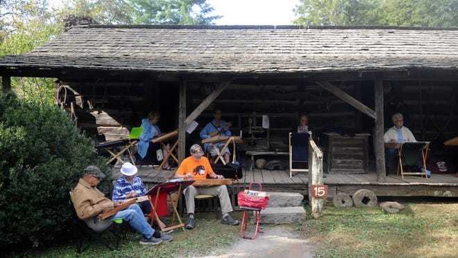 Dulcimer players gather on a porch at the 37th Tennessee Fall Homecoming at the Museum of Appalachia on Saturday, Oct. 8, 2016.