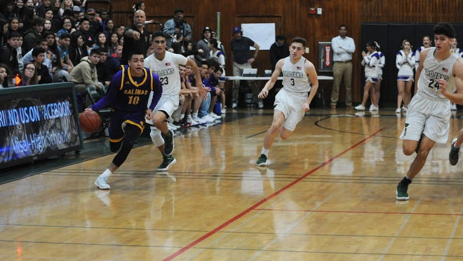 Junior guard AJ Saldana (10) takes the ball in transition for the Salinas Cowboys in the second quarter.