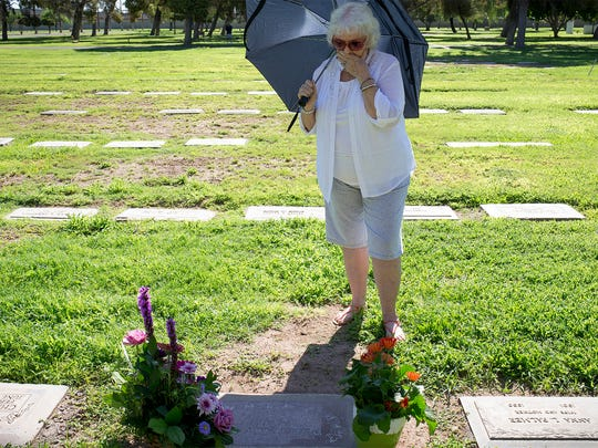 LaVida Calle reacts after seeing her daughter's grave, with a headstone for the first time at Greenwood Memory Lawn Cemetery in Phoenix.