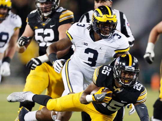 Iowa's Akrum Wadley tries to get past Michigan's Rashan