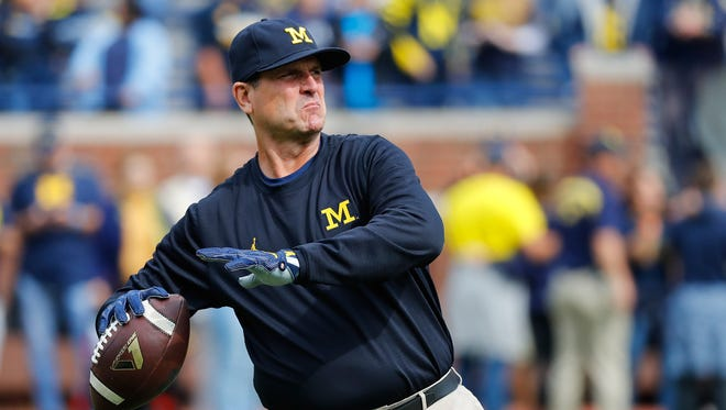 Michigan Wolverines coach Jim Harbaugh throws the ball during warm-ups prior to the game against the Wisconsin Badgers at Michigan Stadium on Oct. 1, 2016 in Ann Arbor.