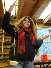 Shannon Pump, naturalist at The Ridges Sanctuary, holds one of the twine-and-pine cone feeders participants could make in the Bird Feeder Workshop.