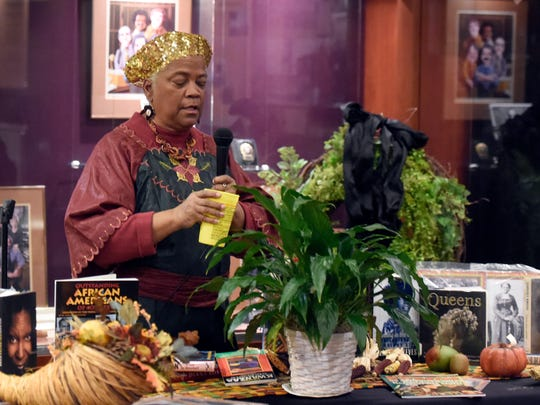 Sondra L. Matthews pours water over a plant during a libation ceremony during the Annual community Kwanzaa Celebration at the Evansville African American Museum Tuesday.