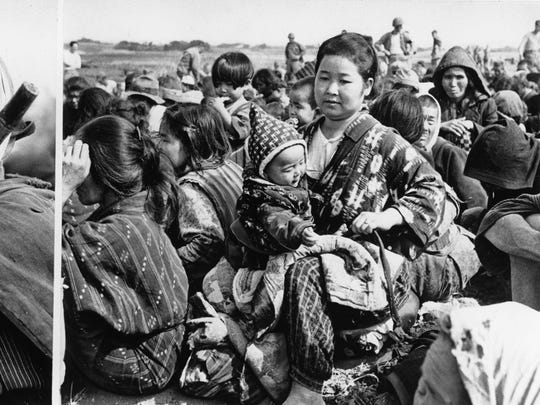 This combination of two photographs shows Japanese residents of Okinawa rounded up by American soldiers, on April 10, 1945.