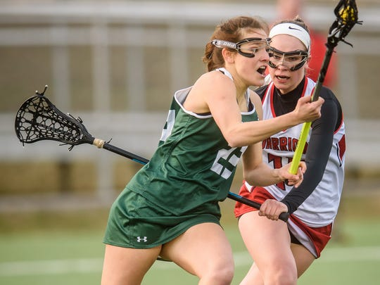 York Catholic's Amanda Tufano (23) moves around Susquehannock's Gena Speights (14) in a girls' lacrosse game on March 24.