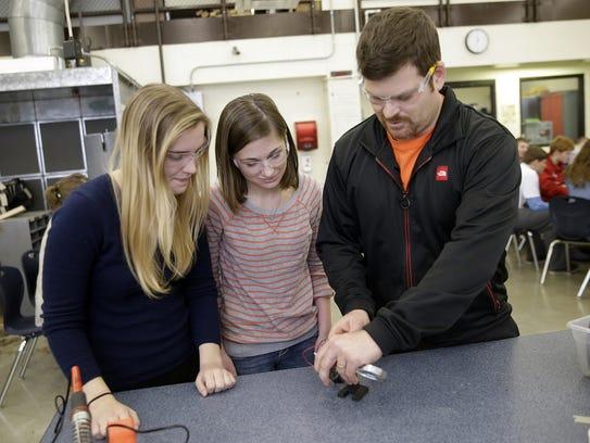 High Schools students work with teacher Jason Shields,