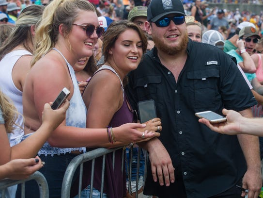 Luke Combs poses for a picture with fans after his