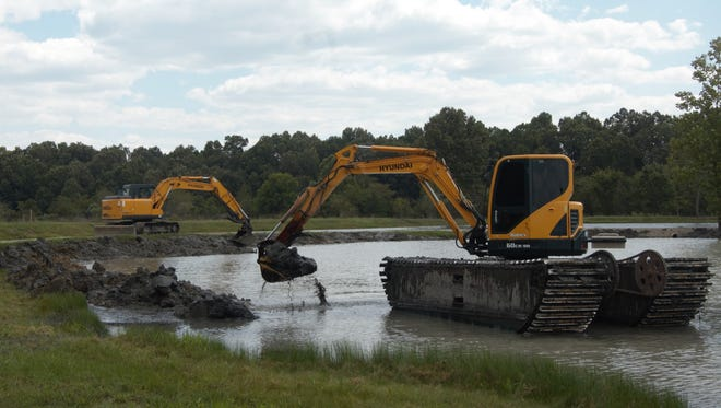 An amphibious excavator on loan to the City of Mountain Home (foreground) works in one of the ponds at McCabe Park while one of the city's excavators works from the bank on Wednesday afternoon.