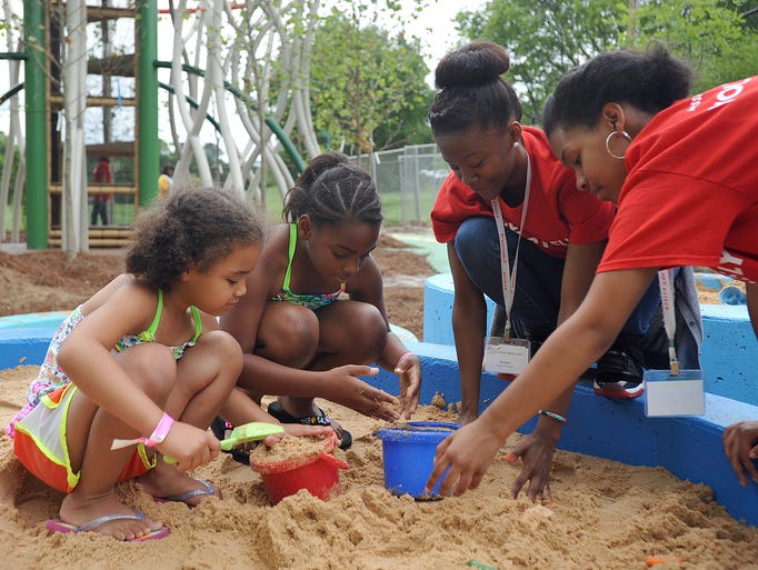 Mississippi Children's Museum volunteers Amber Gillespie, 15, (right) and Coralyn Jones, 15, (second from right) help children Brianna Pinchback, 5 of Texas (left) and Jrace Jamison, 8, of Madison, play in the sand box at the new Literacy Garden at the museum Friday.