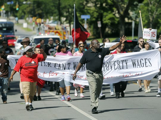 Workers march through Rochester in support of a $15 minimum wage.