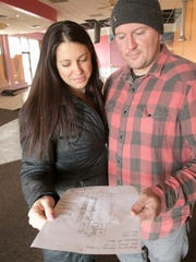 Nikki and Ryan McDonald, shown Wednesday April 4, 2018, consult a layout for Hartland Brewing Company, a new microbrewery they plan to officially open Friday. They have revamped the space since then.