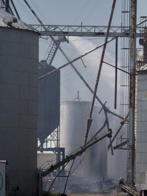 Light smoke continues to come from grain elevators at Fowlerville Farm Services as firefighters pour water from a ladder truck Monday, May, 28, 2018.