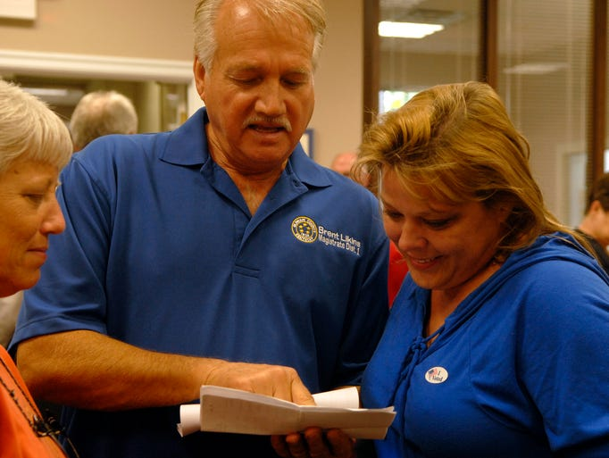 Magistrate District 1, Brent Likins, shows Barbara Winters, right, vote tallies after she heard vote totals in her favor for the PVA election at the Oldham County Fiscal Courthouse.  May 20, 2014