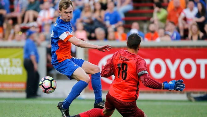 FC Cincinnati midfielder Jimmy McLaughlin (20) is challenged in the penalty box by Tampa Bay Rowdies goalkeeper Matt Pickens (18) in the first half.