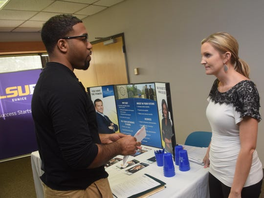 Meredith Lachney (right), center director of the Alexandria Center of Upper Iowa University, meets with Matthew Williams, who holds degrees from NSU and Grambling State University, at the adjunct faculty job fair June 30 at the Learning Center for Rapides Parish located on England Airpark. Williams is looking to teach business courses. Several local colleges and universities were recruiting people to teach as part-time instructors.