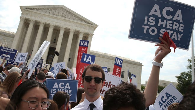 People celebrate in front of the Supreme Court after the ruling was announced on Obamacare subsidies on June 25, 2015.