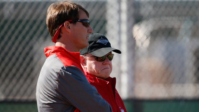 Cincinnati Reds general manager Dick Williams, left, and president of baseball operations Walt Jocketty, right, talk as a handful of position players take batting practice at Cincinnati Reds spring training, Saturday, Feb. 20, 2016, in Goodyear, Arizona.
