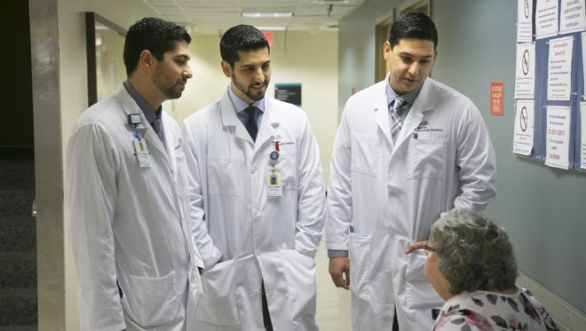 The Abidali brothers, (from left) Ali, Moustapha and Hussein, talk to Residency Coordinator Connie Farrington, (bottom right) following a lecture at Banner University Medical Center in Phoenix.