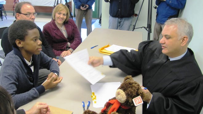 Chemung County Judge Richards W. Rich finalizes the adoption of Rashad Burns, 14, by Clayton and Kitty Ravert of Elmira during the Chemung County Adoption Awareness Month recognition event.