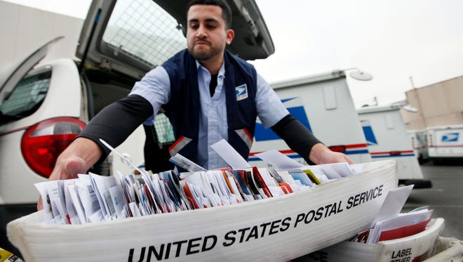 Letter carrier Felipe Raymundo moves a tray of mail to his truck at a post office in Seattle in a 2011 file photo