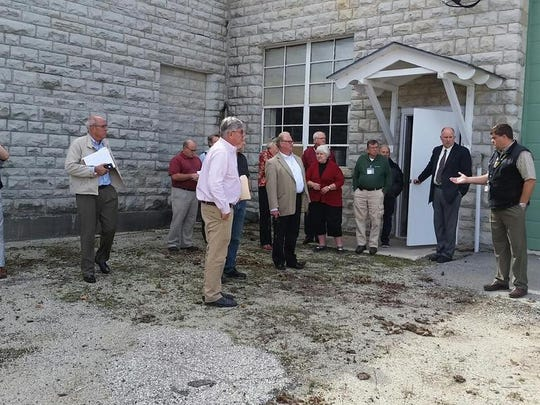 Nearly a dozen architects and building designers are shown the former Door County Highway Shop building on 14th Avenue Tuesday afternoon. County officials want to know whether the building could be remodeled for use as a senior center and as a facility to house the county's Emergency Service ambulances and crews. County Administrator Ken Pabich and Buildings and Grounds Director Wayne Spritka point out the area behind the building the county maintains as a containment site for spills that may have occurred over the years the shops were in use. The county wants to view proposed designs or a recommendation to demolish the complex.