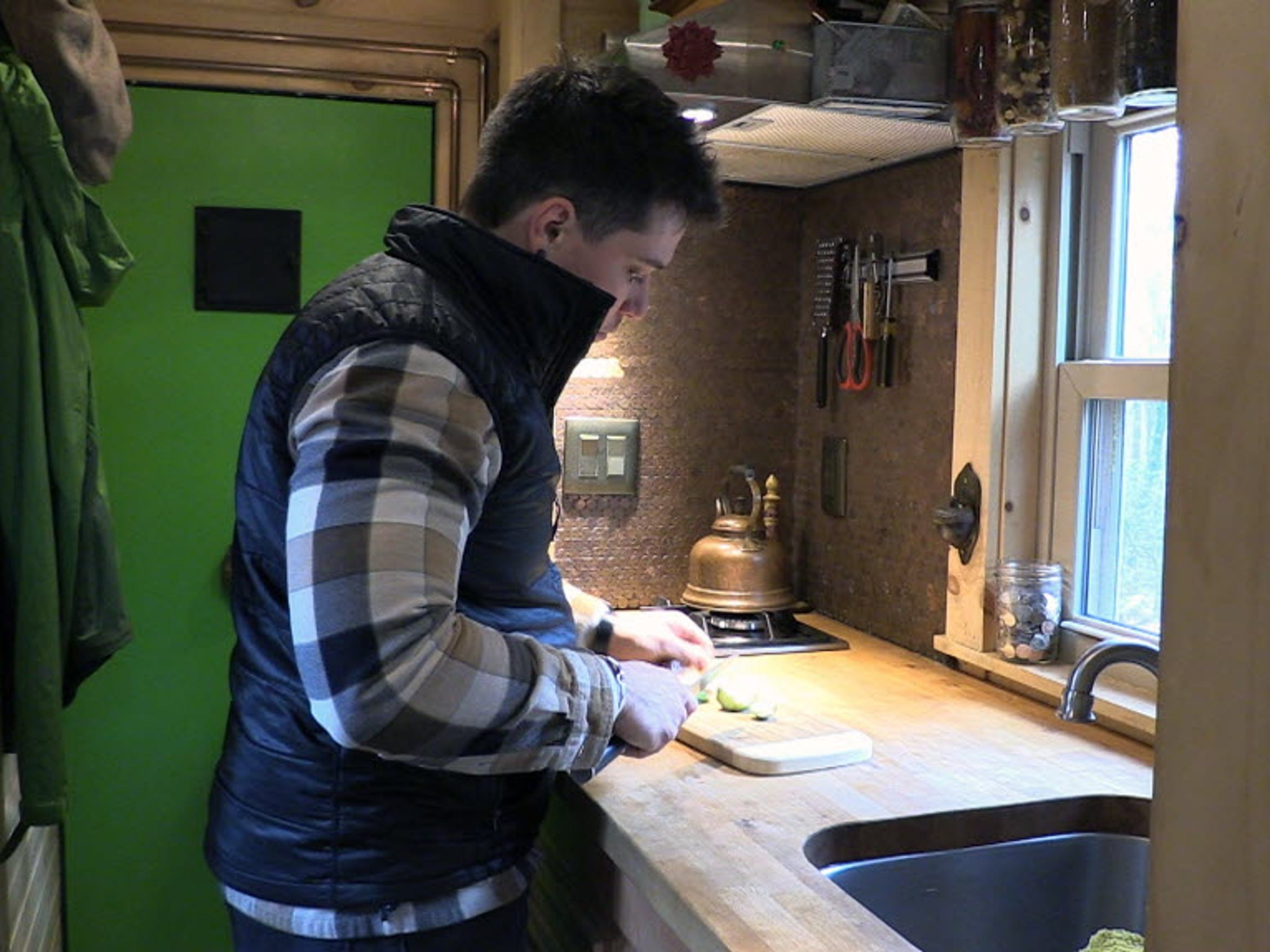Brad Allain shows how he cooks inside his tiny house.