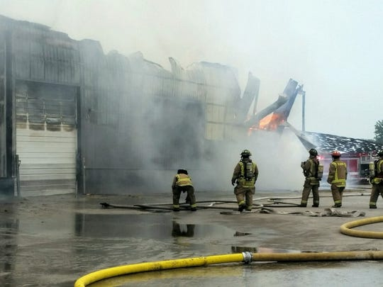 Crews attack a barn fire at Ebert Enterprises on Thursday.