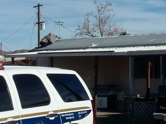 A sniper waits in position during a standoff  Friday between police and a man in an east Phoenix mobile home park.