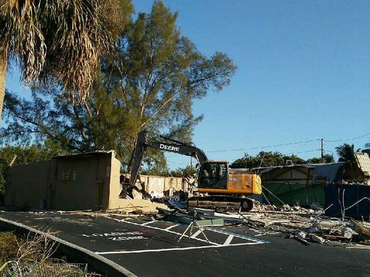 A crew works to demolish the old retail strip at the