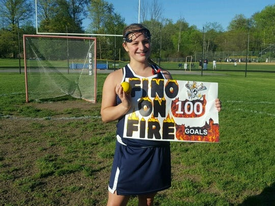 Highland lacrosse player Eliz Fino poses with a poster