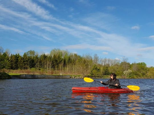 Nancy Nabak of Woodland Dunes Nature Center and Preserve kayaks the West Twin River May 23.