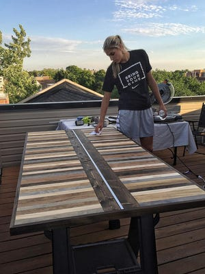 Delaware native Elena Delle Donne works on a table on the rooftop of her Chicago home. The WNBA Chicago Sky star builds furniture when she's not playing basketball.