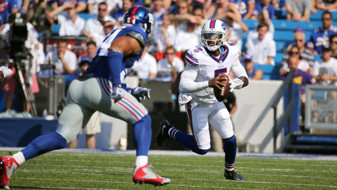 Bills quarterback Tyrod Taylor rolls out looking downfield as Giants Olivier Vernon (54) closes in.