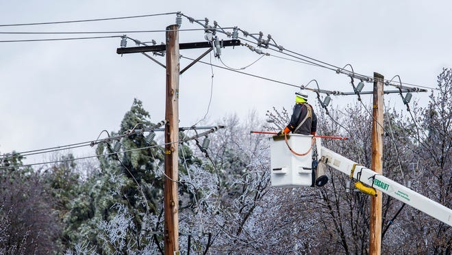Delmarva Power technicians repair power lines in Christiana after sleet and ice brought down trees and lines across New Castle County on Tuesday morning.