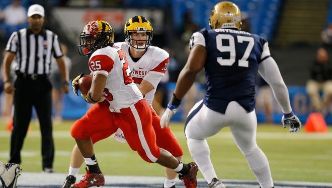 Brandon Ross #25 from Maryland playing on the East Team takes a handoff from Jake Rudock #10 from Michigan playing on the East Team as David Onyemata #97 from Manitoba playing on the West Team defends during the second half of the East West Shrine Game at Tropicana Field on January 23, 2016 in St. Petersburg, Florida.